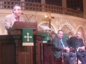 Wilfredo Cancio en el micrófono, miientras José Antonio Évora y Leonardo Padura escuchan, Coral Gables Congrational Church