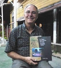 """Emilio Cueto posa con su libro """"La Virgen de Caridad del Cobre en el alma del pueblo cubano"""" en una calle de La Habana"""