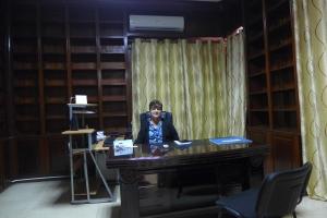 Sentada en el antiguo escritorio de mi padre. Antes estaba colocado en forna diagonal y no estaban las cortinas.
