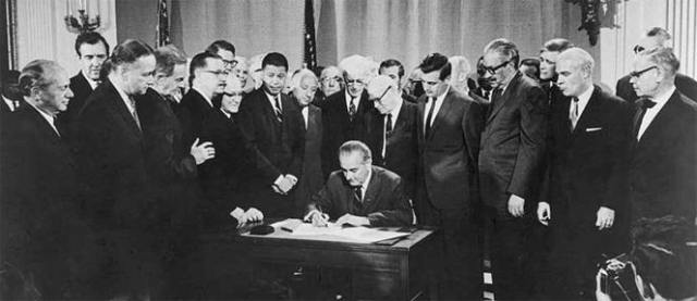 Lyndon b. Johnson durante la firma de la Ley de Derechos Civiles de 1968, otro paso importante en el desarrollo de la democracia