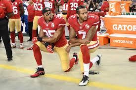 Colin Kaepernick, y uno de sus compañeros en el equipo SanFrancisco 49ers, se arrodillan mientras escuchan el Himno Nacional