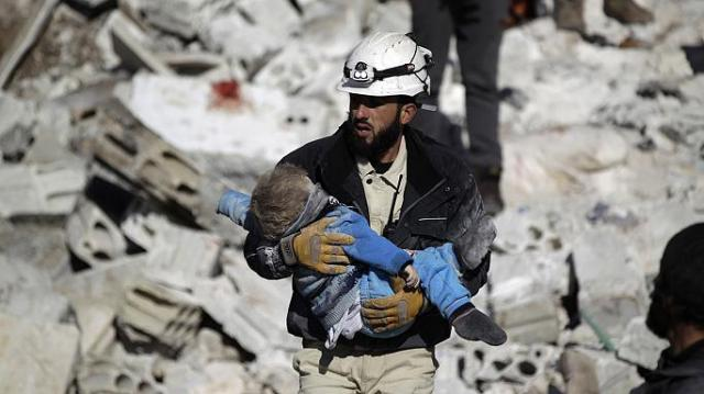 Uno de los cascos blancos lleva a un niño en brazos que han salvado milagrosamente de los escombros